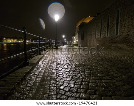 Night shot of wet cobblestone road with glares from lamp in Maastricht, Netherlands.