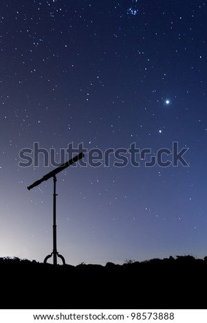 Night shot with a silhouette of a telescope, with a sky full of stars and the conjunction of Venus and Jupiter