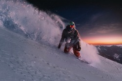 night skating snowboarder curved and brakes spraying loose deep snow on the freeride slope under the starry sky and sunset light