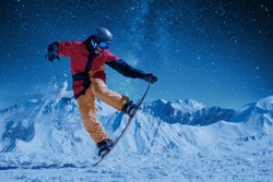 night skating Snowboarder in bright sportswear doing balance trick against of beautiful mountains under the starry sky and moonlight