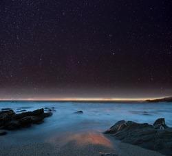 Night sky from a rocky beach. Cornwall, UK.