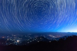 Night sky star trails around the North star with city lights in the background taken from the top of a hill in himalayas