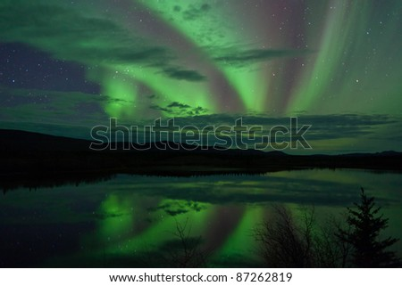 Night Sky Stars, clouds and Northern Lights mirrored on calm lake in Yukon, Territory, Canada.