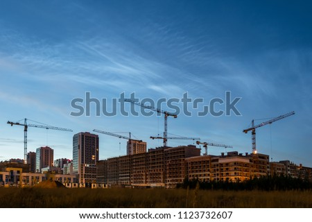 Night sky view of beautiful noctilucent clouds over the city. Cityscape of house building with construsction cranes. Rare phenomena which happens only on summer nights. Cityline with cloudy sky #1123732607