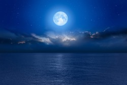 Night sky with Blue moon in the clouds on the fore ground calm blue sea
