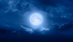 Night sky with full bright moon in the clouds, blue sea in the foreground