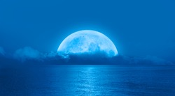 Night sky with moon in the clouds on the foreground calm sea