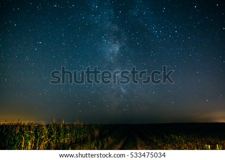 Night sky with the Milky Way and stars over the field