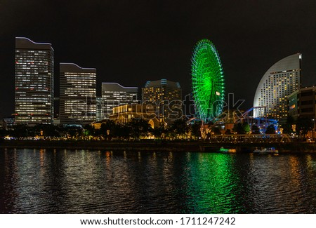 Night skyline of  Yokohama Minato Mirai district with Cosmo Clock 21 ferris wheel illuminated in green, Japan stock photo