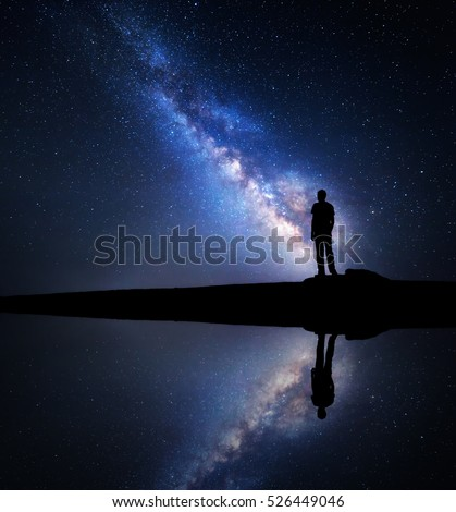 Night starry sky with Milky Way and silhouette of a standing man on the hill near the lake with sky reflection in water. Milky way and man. Galaxy and silhouette of a man. Universe. Space background #526449046