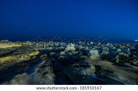 Night stars over rock beach.