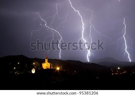 Night storm above a little chapel. Many lightning on the night sky.
