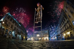 Night street circus performance whit clown balanced in ladder. Festival city background. fireworks and Celebration atmosphere. Wide engle photo
