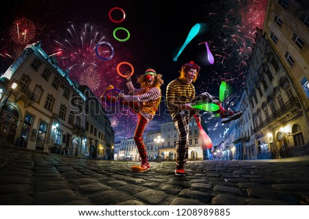 Photo of  Night street circus performance whit two clowns, juggler. Festival city background. fireworks and Celebration atmosphere.