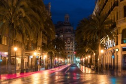 Night street view in Valencia downtown, Spain. Palm Trees in Spanish City of Valencia. Landscape and culture travel, or historical building and sightseeing concept