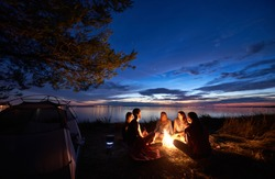 Night summer camping on sea shore. Group of five young tourists sitting on the beach around campfire near tent under beautiful blue evening sky. Tourism, friendship and beauty of nature concept.
