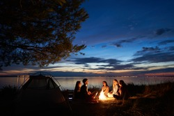 Night summer camping on sea shore. Group of young tourists sitting, laughing in high grass around bonfire near tent under beautiful blue evening sky. Tourism, friendship and beauty of nature concept.