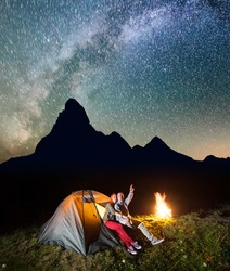 Night tent camping. Charming pair sitting near tent and campfire and enjoying incredibly beautiful starry sky in the background silhouette of the mountains. Long exposure