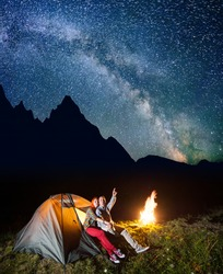 Night tent camping. Young pair sitting near tent and campfire and enjoying incredibly beautiful starry sky in the background silhouette of the mountains. Long exposure