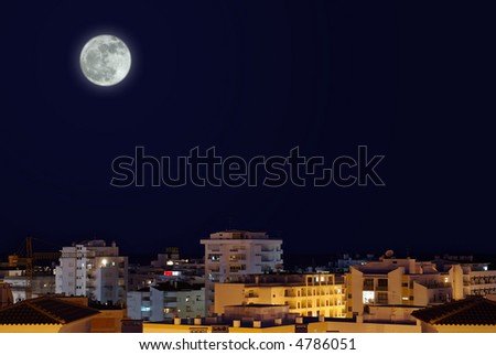 Night-time cityscape with full-moon in the sky. - stock photo