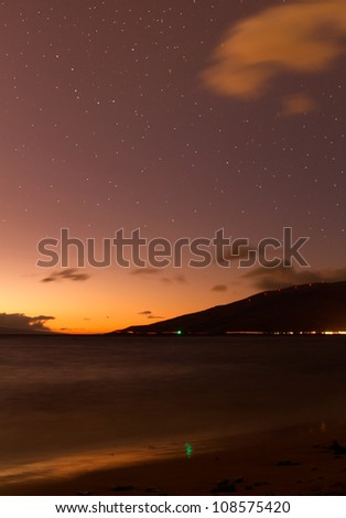Night time shot of Maui with ocean blur and stars