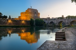 Night to sunrise long exposure of Castel Sant Angelo (Castle of the Holy Angel), an ancient tomb and fortress illuminated and reflecting on the Tiber river, with the Bridge of the Holy Angel