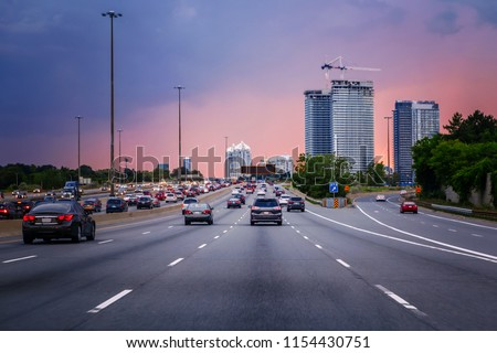 Night traffic. Cars on highway road at sunset evening in typical busy american city. Beautiful amazing night urban view with red, yellow and blue sky clouds. Sundown in downtown. #1154430751