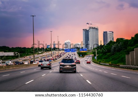 Night traffic. Cars on highway road at sunset evening in typical busy american city. Beautiful amazing night urban view with red, yellow and blue sky clouds. Sundown in downtown. #1154430760