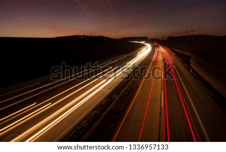 Night urban scene of motion blurred light tracks glowing to the darkness of highway traffic transport to the city just after sunset. Creative long time exposure diagonal composed photography. #1336957133