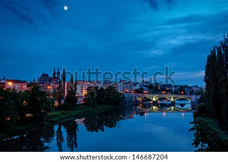 night vieew of St. Bartholomew Gothic Cathedral and old bridge over Elbe river in Kolin, Czech Republic