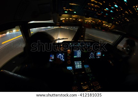 Night view from the airplane cockpit. The aircraft is moves for take off from the airport runway.