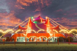 Night view of a circus tent under a warn sunset and chaotic sky