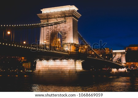 Night view of a famous Budapest Szechenyi Chain Bridge, a suspension bridge that spans the River Danube between Buda and Pest, the western and eastern sides of Budapest #1068669059