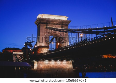 Night view of a famous Budapest Szechenyi Chain Bridge, a suspension bridge that spans the River Danube between Buda and Pest, the western and eastern sides of Budapest #1068669071