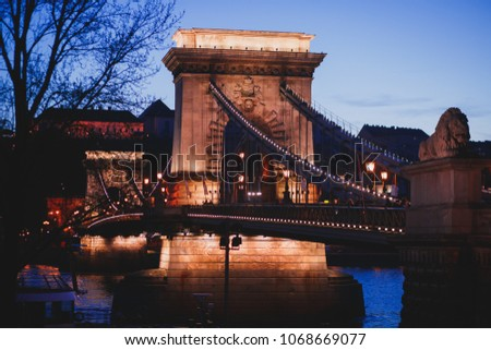 Night view of a famous Budapest Szechenyi Chain Bridge, a suspension bridge that spans the River Danube between Buda and Pest, the western and eastern sides of Budapest #1068669077