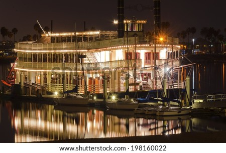 Night view of an authentic,vintage,American riverboat with two chimneys resembling the steamboats used in 1800s in Mississippi river. A view of Mission Bay and pier,San Diego,southern California,USA.