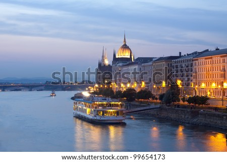 Night view of Budapest with small cruise boat