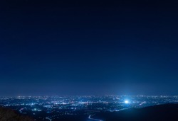 night view of city and starry sky from mountainside