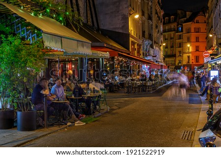 Night view of cozy street with tables of cafe in Paris, France. Architecture and landmarks of Paris. Postcard of Paris