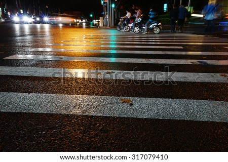 Night view of Crosswalk and pedestrian at modern city zebra crossing street in rainy day. Blur abstract.
