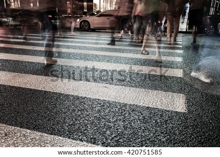 Night view of Crosswalk and pedestrian at modern city zebra crossing street in rainy day. Blur abstract. #420751585
