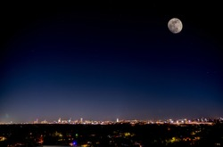 Night View of Downtown Austin Texas With Large Moon on the Dark Sky