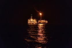 Night view of FPSO tanker vessel near Oil Rig. Offshore oil and gas industry. Flare boom is brightly burning.