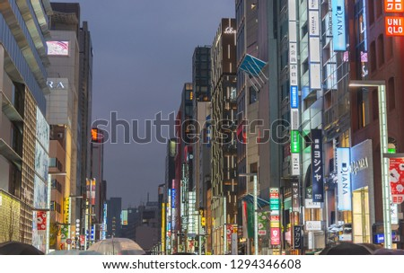Night view of Ginza District, The district has famous brand flagship stores everywhere, offers high end retail shopping. Text in Japanese advertise stores name. #1294346608