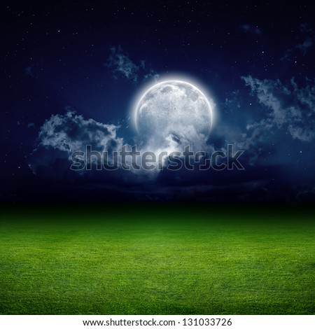Night view of green grass field. Dark sky with white clouds, moon and stars. Elements of this image furnished by NASA