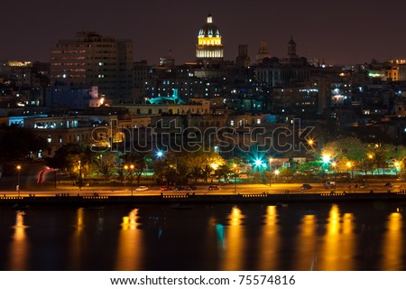 Night view of Havana including the Capitol, other famous buildings and the bay with reflection on the water