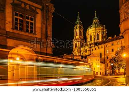 Night view of illuminated Church of Saint Nicholas,Malostranske namesti,Prague,Czech republic.Lesser Town of Prague.Long exposure lights. Movement of tram.Traffic light.Night city scene.Travel concept