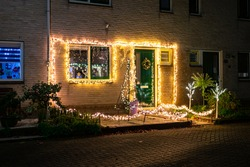 Night view of many lights on the front of a house in a Dutch town. Christmas decoration.
