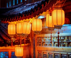 Night view of row of traditional Chinese red street lanterns on carved facade of wooden house in the Old Town of Lijiang, Yunnan province, China. Focus on the first lantern.