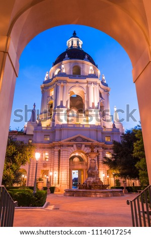 Night view of the beautiful facade and courtyard of the historical City Hall building of Pasadena framed by an exterior arch, Los Angeles county, California; the building was completed in 1927